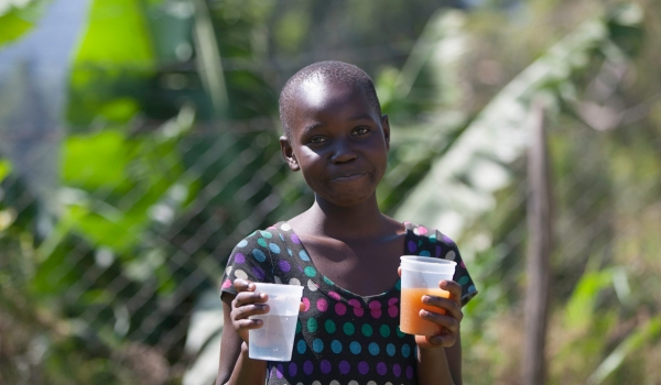 Girl showcases harvested river water and filtered water sold at kiosk (Karim photography(c)2020)